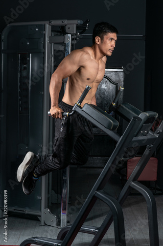 Spoed Foto op Canvas Fitness Muscular bodybuilder working out in gym doing exercises on parallel bars. Athletic male naked torso