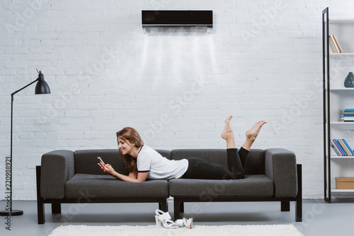 Valokuva  happy young woman using smartphone on couch under air conditioner hanging on wal