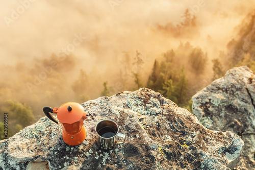 ekspres do kawy i kawa w filiżance w pobliżu kempingu na tle gór mglistych