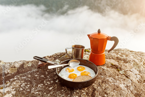 breakfast meal Fried eggs in pan and coffee geyser maker outdoors in mountains, camping food concept