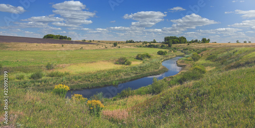 Sunny summer landscape with river,fields,green hills and beautiful clouds in blue sky.River Upa in Tula region,Russia.
