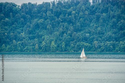 Beautiful sailing ship on silent water of green lake