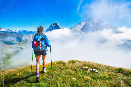 Photo  A girl during a hike in the mountains with poles sticks
