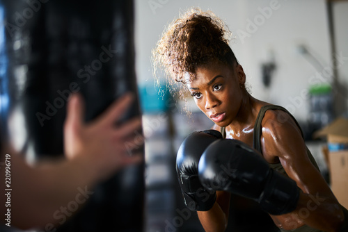 African woman boxing with punching bag in garage gym buy this