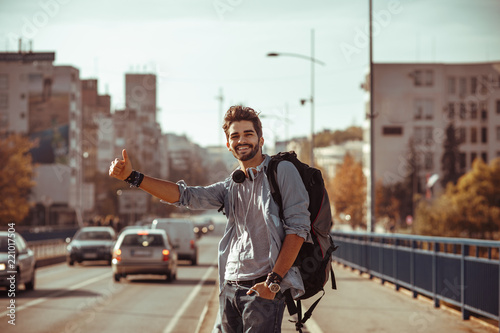 Young man traveler hitchhiking in the city