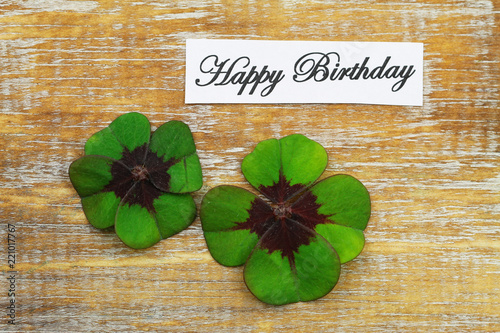 Photo  Happy birthday card with two four-leaf clovers on rustic wooden surface