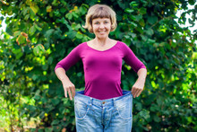 Young Woman Wearing Big Loose Jeans With Apple In Hand - Weight Loss Concept