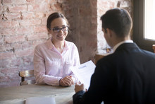 HR Manager Interviewing Young Smiling Woman Student In The Office. Male Wearing Suit Holding Curriculum Vitae Sitting. Positive Atmosphere, Successfully Passing The Interview, Confident Girl