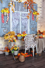 Autumn Decoration At Home. Basket With Golden And Yellow Wilted Flowers, Orange Leaves, Autumn Vegetables. Window Is Decorated With Autumn Decor.