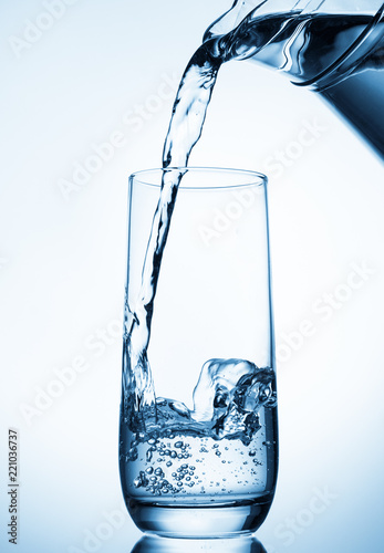 Fotografia  Pouring water from glass pitcher on blue background