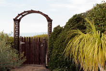 Natural Wood Picket Gate Opens To Distant View Of Opportunity Or Mystery, Surrounded By Green Foliage