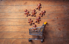 Gingerbread Cookie And Shopping Cart On Wooden Table