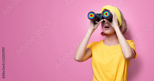 Fotografia  Young redhead girl in yellow t-shirt and blue jeans holding binoculars on pink b