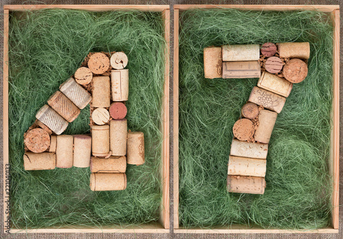Fotografia  Number 47 forty seven  made of wine corks on green background in wooden box