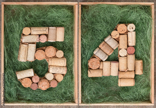 Fotografia  Number 54 fifty four  made of wine corks on green background in wooden box