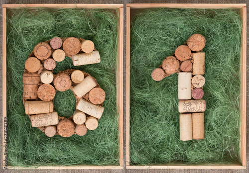 Fotografia  Number 61 sixty one  made of wine corks on green background in wooden box