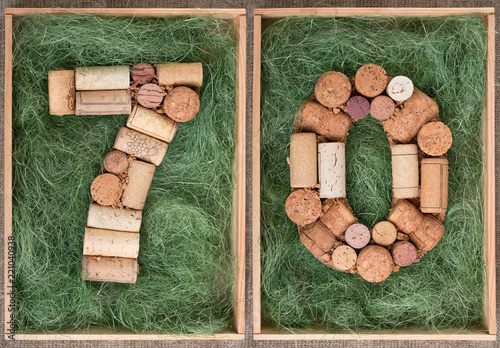 Fotografia  Number 70 seventy  made of wine corks on green background in wooden box