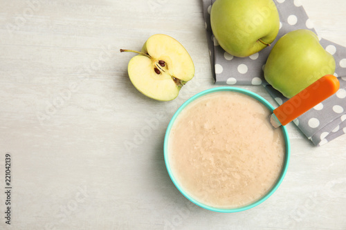Fotografía  Flat lay composition with bowl of healthy baby food and space for text on light