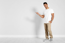 Full Length Portrait Of Handsome Young Man And Space For Text On White Wall Background