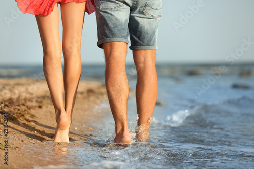 Fotografia  Young couple spending time together on beach, closeup of legs