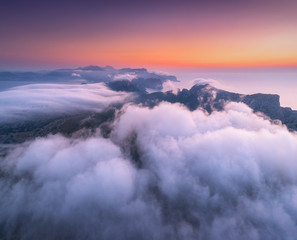 Fototapeta Niebo Aerial view of low clouds, mountains, sea and colorful sky at sunset. Above the clouds at dusk. Seashore in Spain. Top view from drone. Amazing landscape with cloudy sky and rocks. Nature background