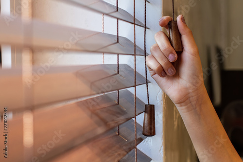 Fotomural  The woman's right hand holds one of the control strings of the wooden shutters on the window