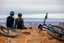 A Young Mountain Biking Couple Takes A Minute To Take In The Scenery