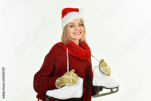 Papiers peints Glisse hiver Woman in Santa hat, red sweater and mittens with ice skates. Smiling girl wearing santa claus hat getting ready for ice skating. Ice skating girl. Winter sport. Girl in winter clothes with ice skates.