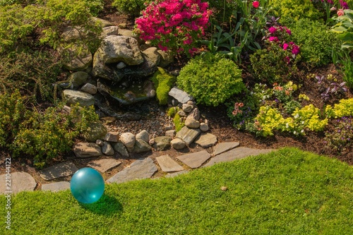 Papiers peints Jardin Backyard garden stone fountain with bright turquoise blue childhood toy ball in spring sunlight