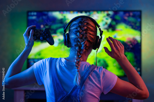 Fotografie, Obraz  A gamer or a streamer girl at home in a dark room with a gamepad playing with friends on the networks in video games