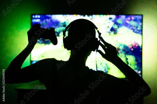 Photo  girl gamer in headphones in the dark on tv background