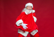 Christmas. A Kind Smiling Santa Claus Is Holding A Red Bag With Presents In Front Of Him Embracing It. Isolated On Red Background.