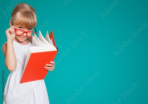 фотография  Education and school concept -  little student girl with book at