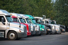 Different Big Rig Semi Trucks Tractors Stand In Row On Parking Lot With Green Trees