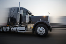 Profile Of Dark Bonnet Classic Big Rig Semi Truck Going On The Road With Sunshine