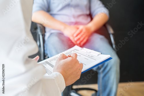 Fotografering Male doctor and testicular cancer patient are discussing about testicular cancer test report