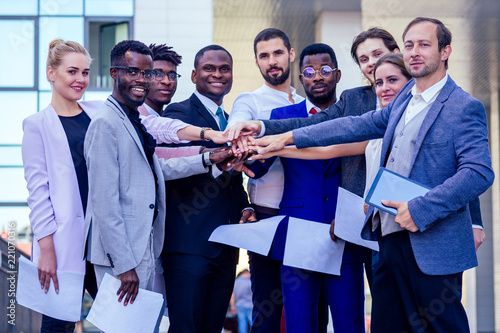 Fotografia, Obraz  a group of nine multinational people businesswomen and business men in stylish suits work in a team outdoors