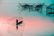 Silhouette Of Fishermen Using Coop-like Trap Catching Fish In Lake With Beautiful Scenery Of Nature Morning Sunrise. Beautiful Scenery Along Seashore.