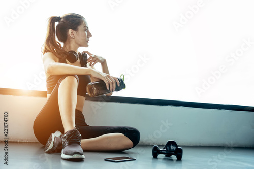 Fototapeta Asian woman exercising in the gym, Young woman workout in fitness for her healthy and office girl lifestyle. She using smart phone to check an email or listening music. obraz