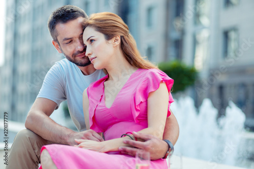 Keuken foto achterwand Ontspanning Strong feelings. Pleasant married couple sitting near the fountain while hugging each other