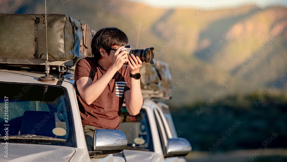 Fototapety, obrazy: Young Asian male traveler and photographer sitting on the car window taking photo on road trip in Namibia, Africa. Travel photography concept