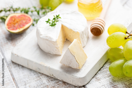 Camembert or brie cheese with grapes, figs and honey on white wooden serving board. Closeup view, selective focus