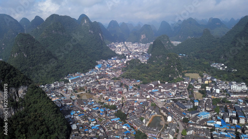 Fotografiet aerial view of town between green hills in Indonesia