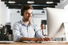 Photo Of Businesslike Man 20s Wearing Office Clothes And Headset, Working On Computer In Call Center