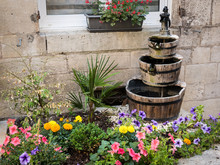 Small Flowerbed In Front Of A Window With A Fountain