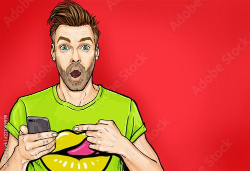 Atrakcyjny zadziwiający młody człowiek wskazuje palec na telefonie komórkowym w komiczka stylu. Pop-art zaskoczony facet trzyma smartphone.