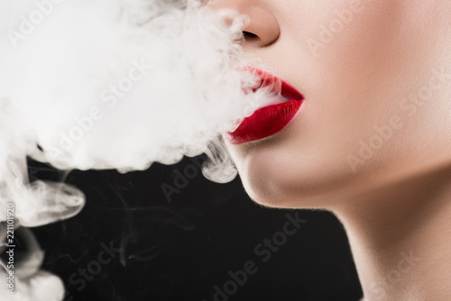 Fototapeta cropped view of smoking woman blowing smoke, isolated on grey obraz