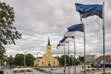 National Flags Of Estonia Waving At Freedom Square Near The Church Of St. John, In The Historical Center Of Tallinn