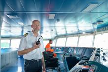 Portrait Of Ship's Captain On Bridge Onboard Ship In Port