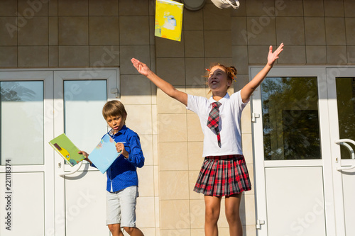 Fotografie, Obraz  Children happily run from school and throw up books after the end of lessons